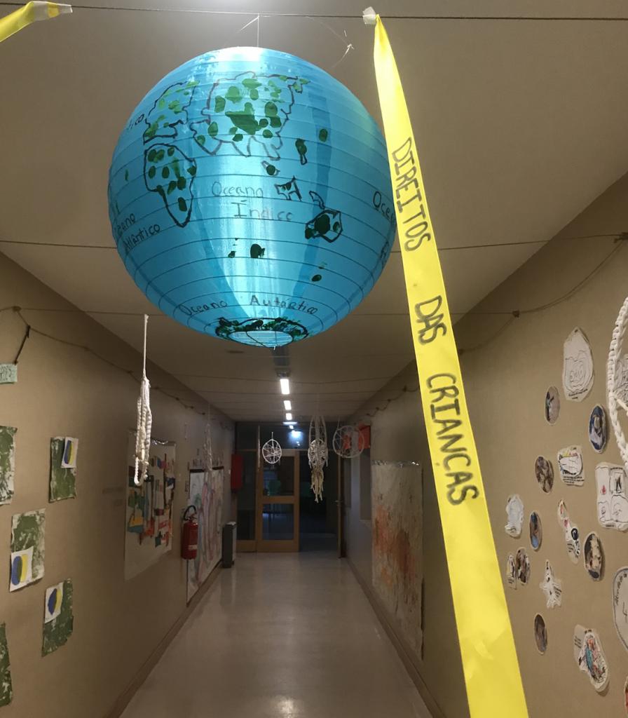Globo terrestre pintado por crianças enfeitando corredor