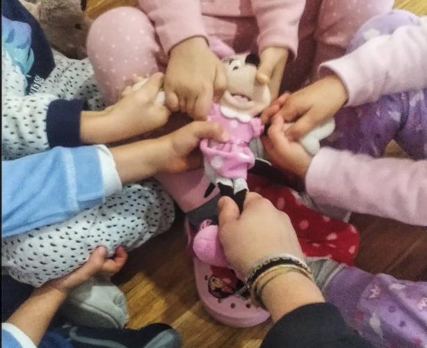 Crianças sentadas, disputando uma boneca