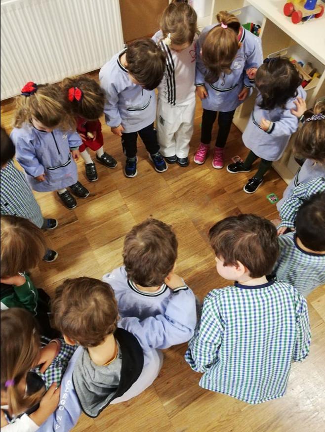Crianças em roda, olhando o chão